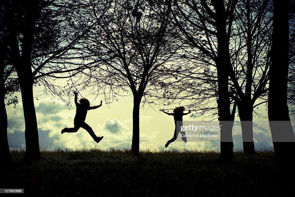 Two silhouettes jumping joyfully in forest : Stock Photo