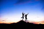 Two Silhouettes of males jumping on beach at sunset