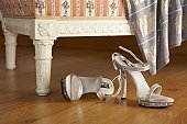 two silver high-heeled womans sandals on wooden floor, close-up