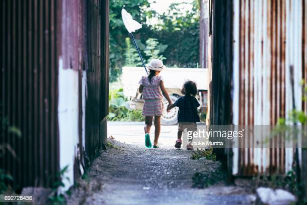 Two sister holding hands and walking with butterfly net
