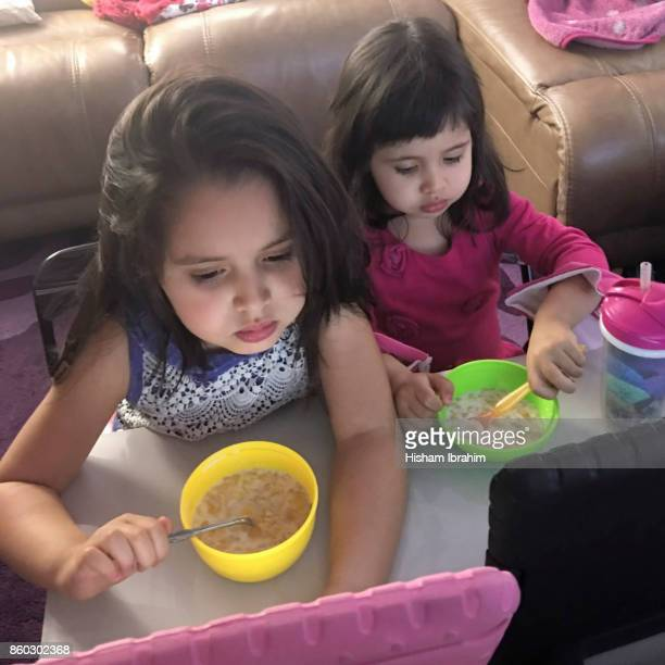 Two sisters 3 years and 5 years eating breakfast cereal and watching digital tablet at home.