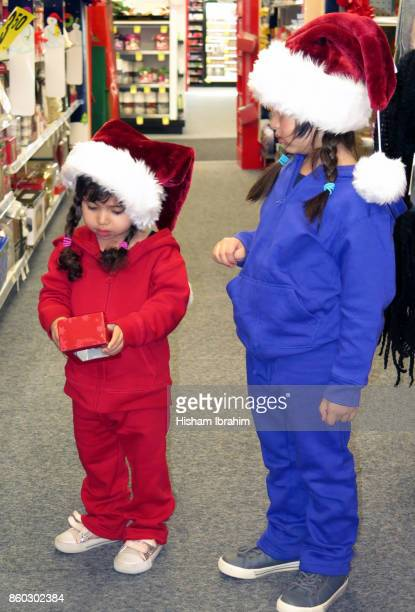 Two sisters 3 years and 5 years wearing Santa hat and shopping for Christmas gifts and decorations at store.