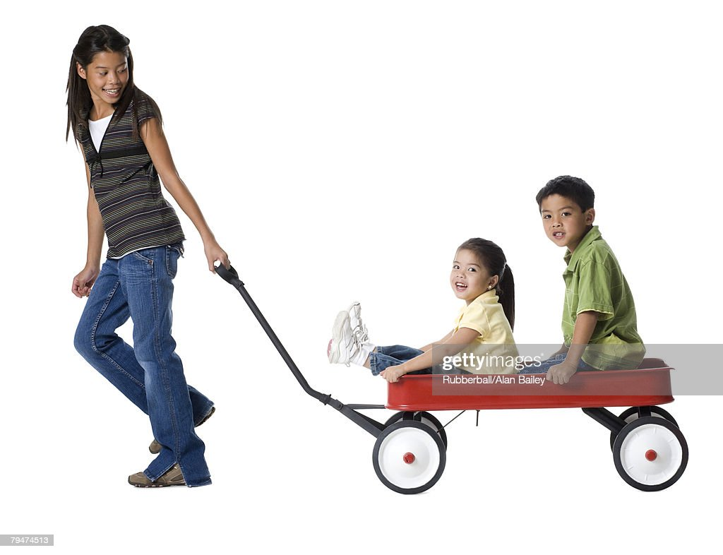 Two sisters and a brother in a wagon : Stock Photo
