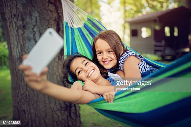 Two sisters are lying down in the hammock and taking selfie/video call