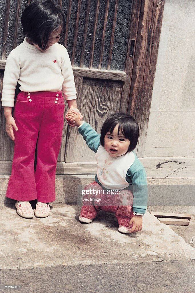 Two sisters at door step : Stock Photo