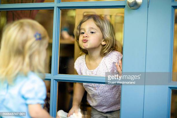 Two sisters (20 months-3) at French doors, one girl kissing window