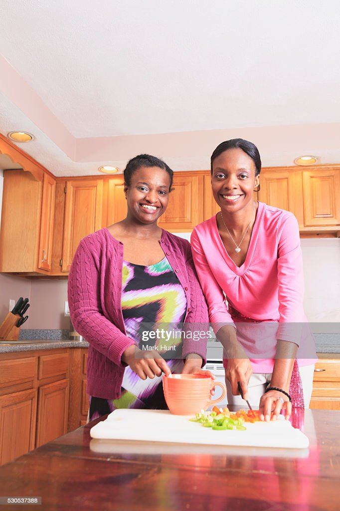 Two sisters cooking in the kitchen, one with learning disability