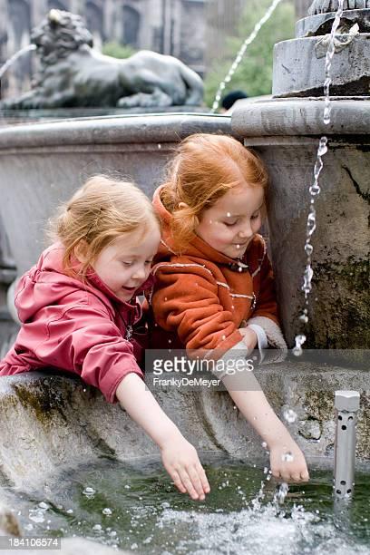 Deux sœurs s'amuser avec une fontaine