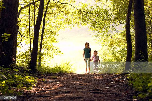 Two Sisters Holding Hands and Standing at Edge of Forest