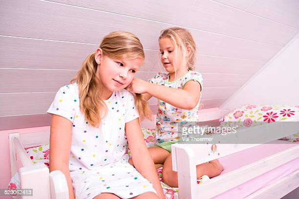 Two sisters in bed, doing their hair