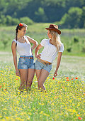 Two young woman in shorts posing in medow