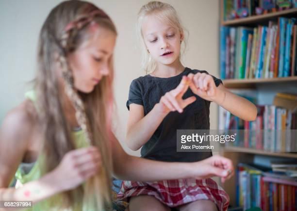 Two sisters in kids room, oldest sister make hair dress.