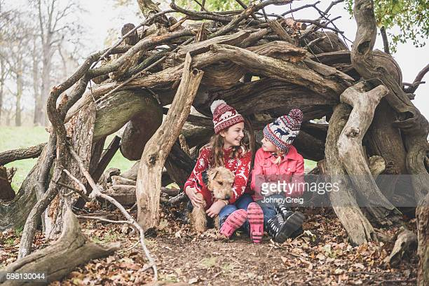 Two sisters in winter clothes in log den with dog