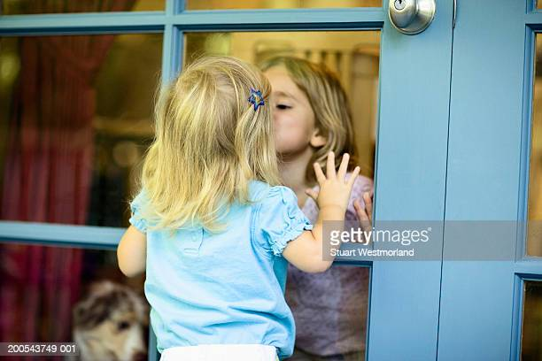 Two sisters (20 months-3) kissing each other through French door