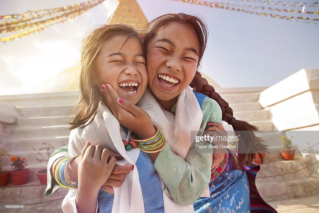 two sisters laughing by the steps of Boudha temple
