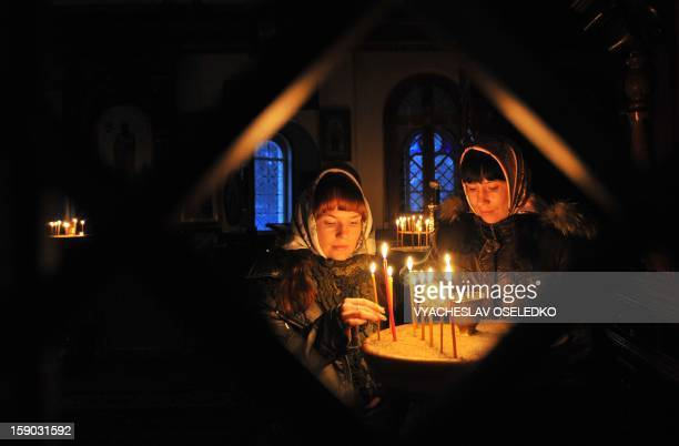 Two sisters light candles during an Orthodox Christmas service in a church in the village of Sokuluk some 30km outside Bishkek on January 6 2013...
