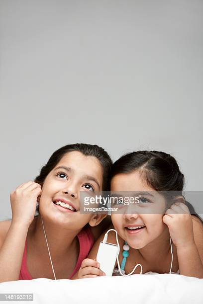 Two sisters (6-11) listening to music on mp3 player