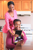 Two sisters looking at a digital tablet in the kitchen, one with learning disability