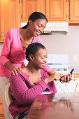 Two sisters looking at a smartphone in the kitchen, one with learning disability