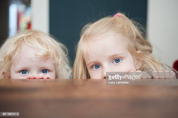 Two sisters looking just above the table