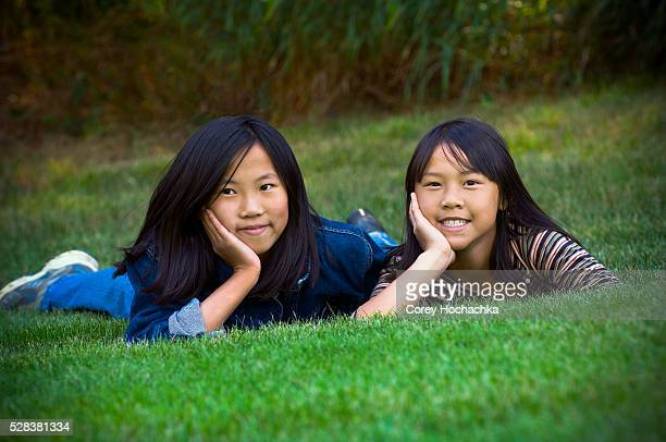 Two sisters lying in the grass
