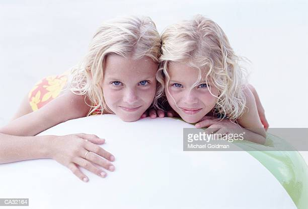Two sisters (4-7) lying on large beachball on beach, portrait
