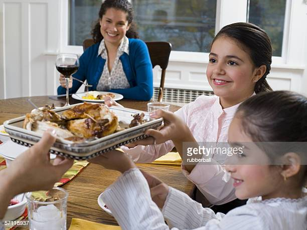 Two sisters passing a tray of food at a dinning table