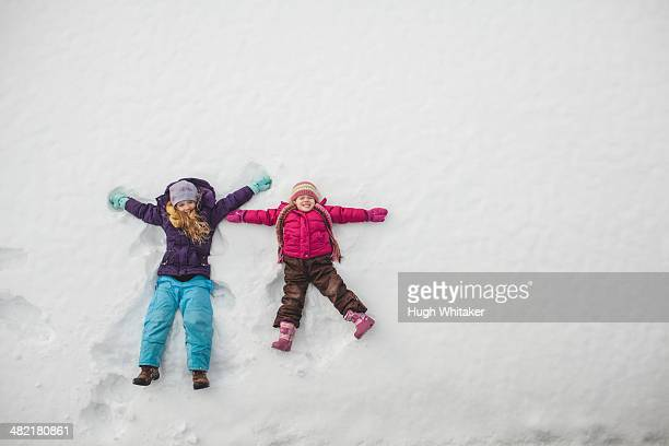 Two sisters playing, making snow angels in snow