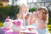 Adorable little sisters dressed like princesses playing tea party. Beautiful decorated tea party outdoors, at the backyard.