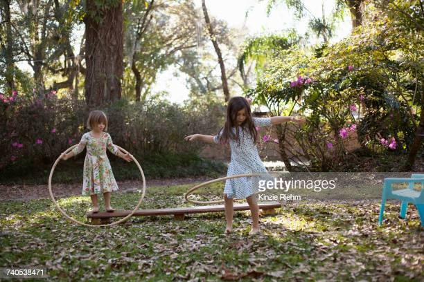 Two sisters playing with plastic hoops in shaded garden