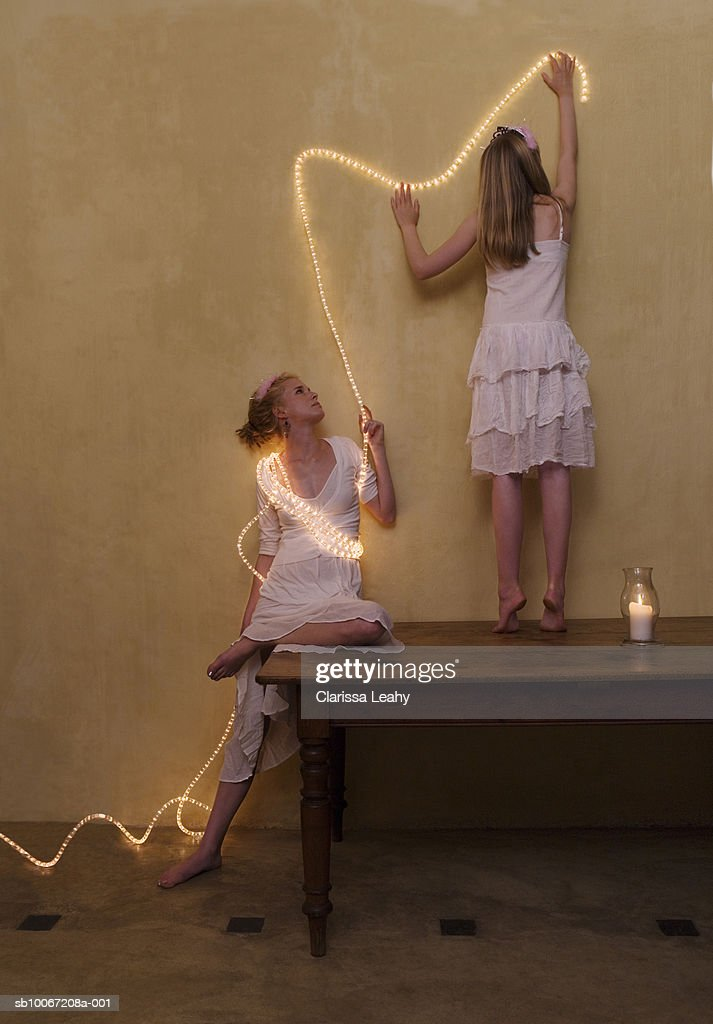 Two sisters putting fairy lights on wall : Stock Photo