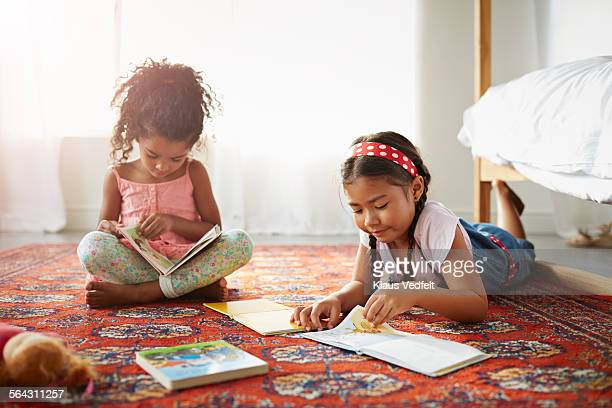 Two sisters reading books on the floor in bedroom