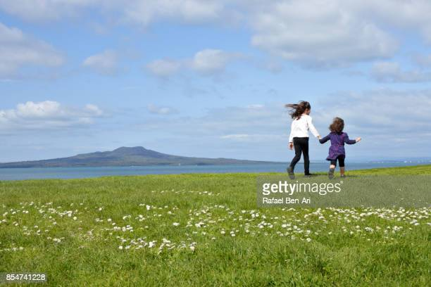 Two sisters running together outdoors on a green field