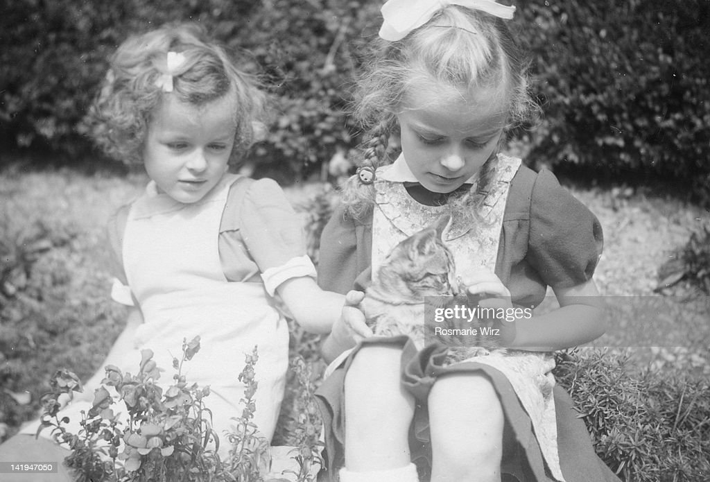 Two sisters sitting in garden and playing with cat : Stock Photo