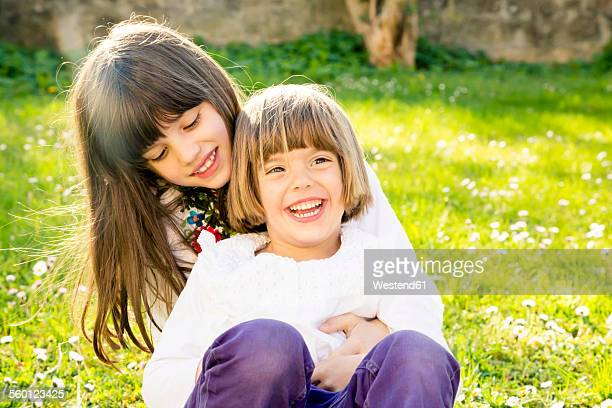 Two sisters sitting together on a meadow in the garden