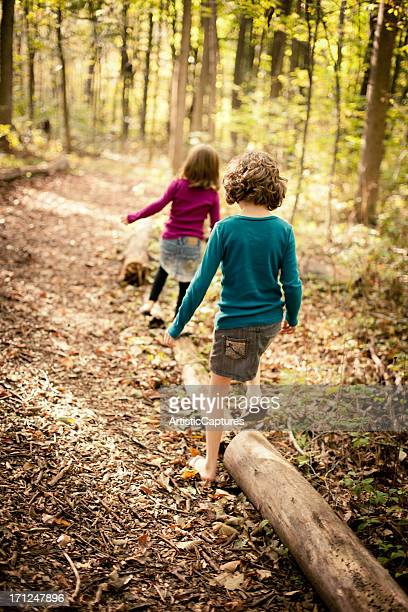 Two Sisters Walking Through Woods Together on Autumn Day