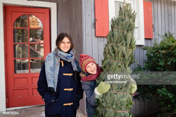 Two sisters with freshly cut Christmas tree in front of house outdoors.