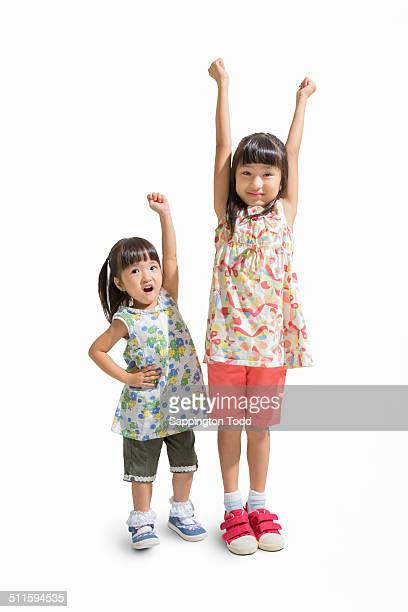 Two Sisters With Hand Raised