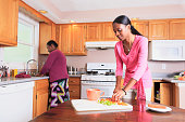 Two sisters working in the kitchen, one with learning disability