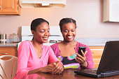 Two sisters working with smartphone and laptop at home, one with learning disability