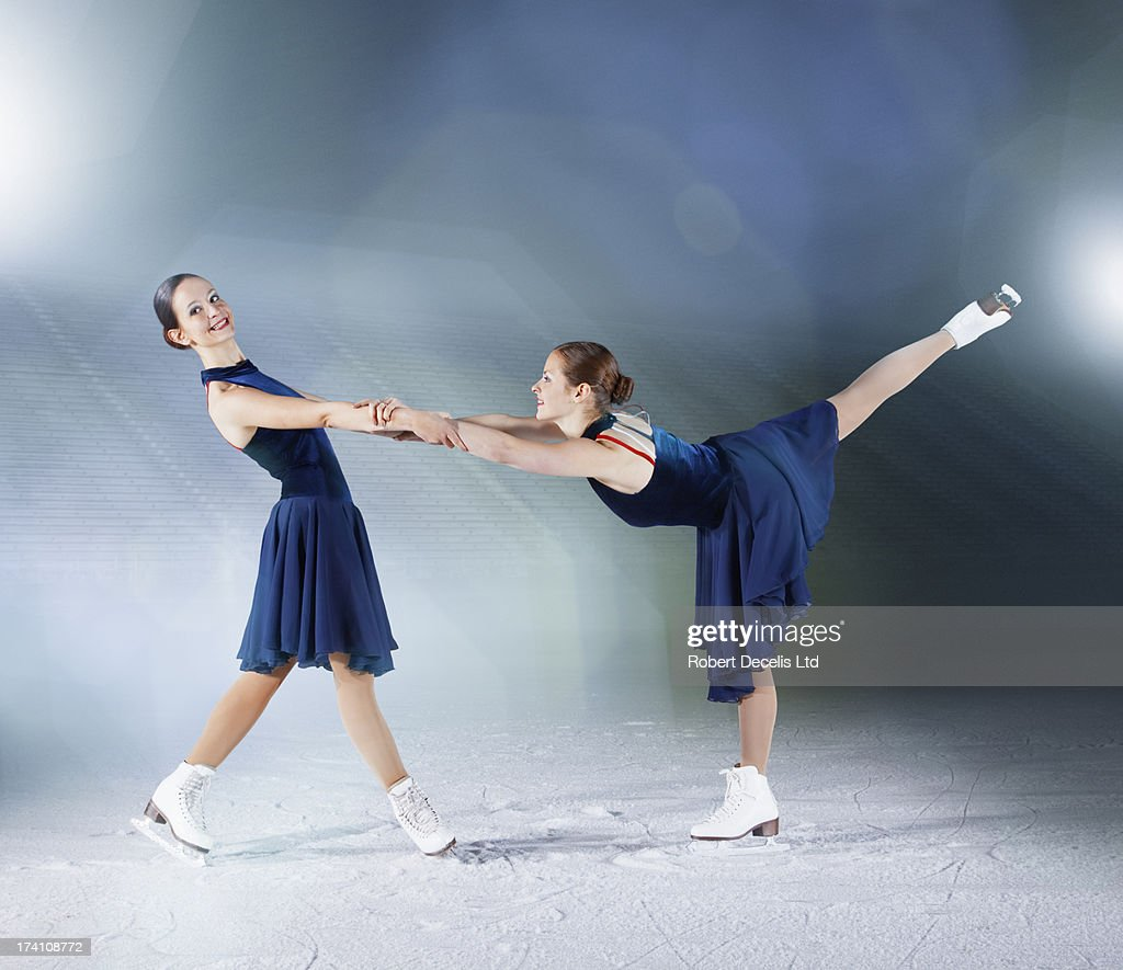 Two skaters, one supporting the other. : Stock Photo