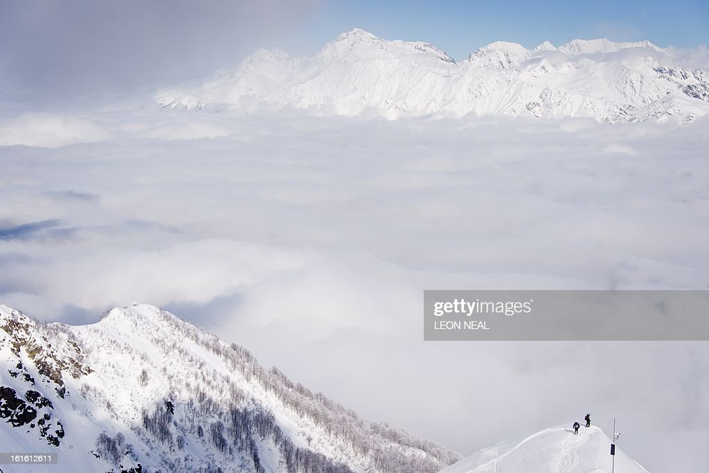 Two skiers approach a high precipice on Mount Aigba in the Rosa Khutor Extreme Park, some 50 km from Russia's Black Sea resort of Sochi, on February 13, 2013. With a year to go until the Sochi 2014 Winter Games, construction work continues as tests events and World Championship competitions are underway.