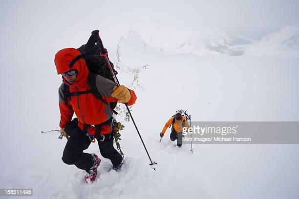 Deux skieurs gravir une pente sur un jour nuageux et neige