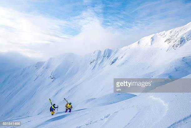 Two skiers climbing up a snow-covered hill