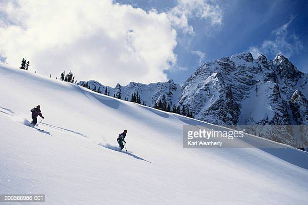 Two skiers on ski slope, Jasper National Park, Alberta, Canada