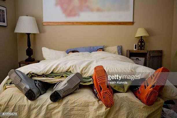Two skiers sleep with ski boots on.