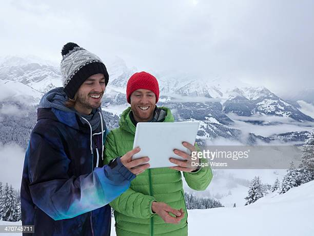 Two skiers using digital tablet in The Alps.