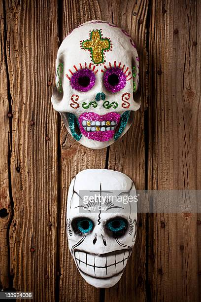 Two skull masks on wooden wall