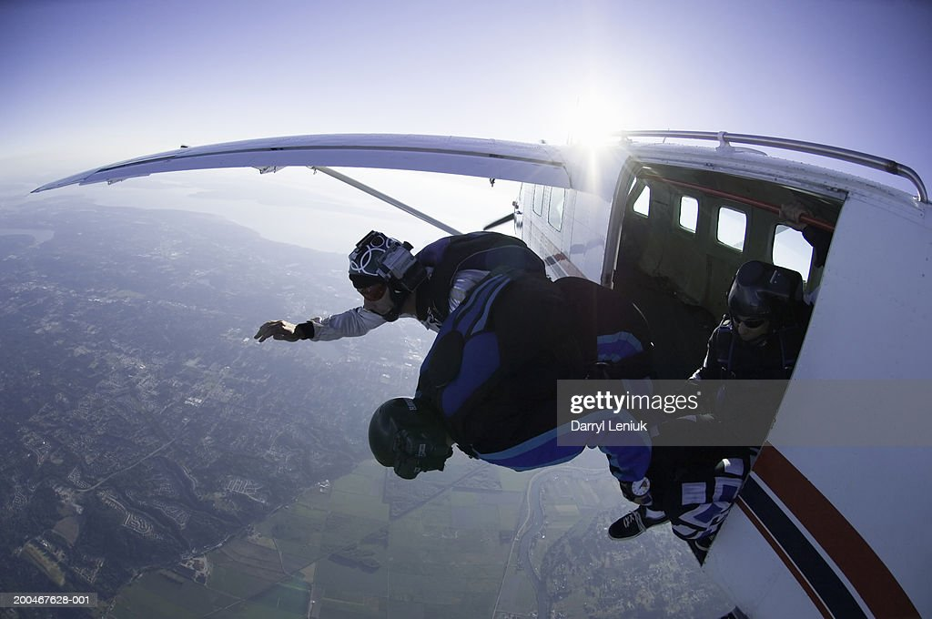 Two skydivers jumping out of airplane, aerial view