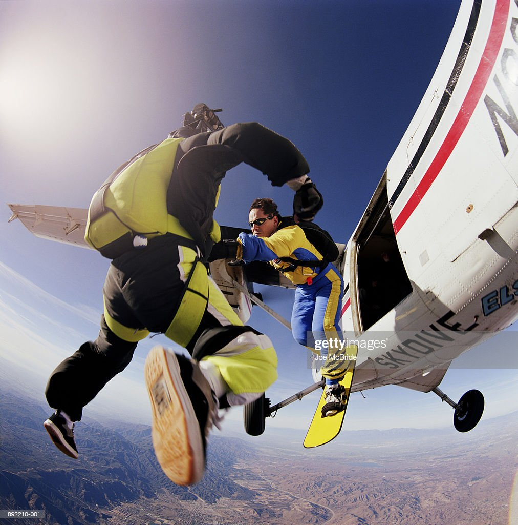 Two skysurfers jumping out of plane : Stock Photo
